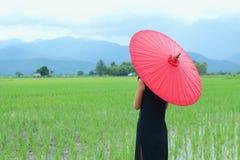 Frauen kleideten im Schwarzen mit einem roten Regenschirm an Stockfoto
