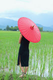 Frauen kleideten im Schwarzen mit einem roten Regenschirm an Lizenzfreies Stockfoto