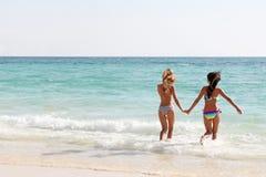 Frauen laufen gelassen zum Meer Stockfotos