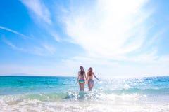Frauen laufen gelassen zum tropischen Meer Stockbilder