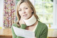 Frauen-Lesebuchstabe, nachdem Nackenverletzung empfangen worden ist Lizenzfreies Stockfoto