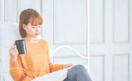 Frauen lesen ein Buch, das ein schwarzes Glas hält lizenzfreie stockfotos