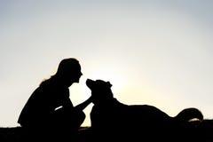 Frauen-Liebkosungs-Hund außerhalb des Schattenbildes Stockfotos