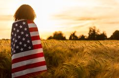 Frauen-Mädchen-Jugendlicher eingewickelt in USA-Flagge auf dem Gebiet bei Sonnenuntergang Lizenzfreie Stockfotografie