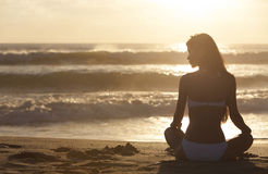 Frauen-Mädchen-sitzender Sonnenaufgang-Sonnenuntergang-Bikini-Strand Stockfoto