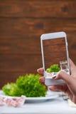 Frauen macht Foto mit smarphone mit Diätkonzept auf Schirm Lizenzfreie Stockfotografie