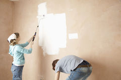 Frauen-Malerei und Mann, die in Unrenovated-Haus verbiegen lizenzfreies stockfoto