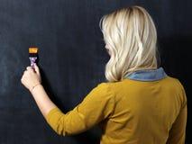 Frauen-Malereiwand mit Malerpinsel Lizenzfreie Stockfotografie