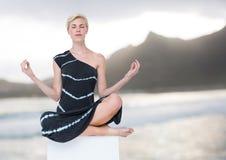 Frauen-Meditieren ruhig durch Berge stockfotografie