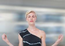 Frauen-Meditieren ruhig gegen Bewegungsunschärfehintergrund stockfoto