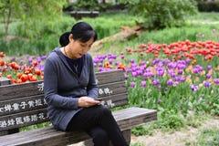 Frauen mit beweglichem Internet im Park Lizenzfreies Stockfoto