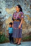Frauen mit dem Kind, das traditionelle Mayakleidung trägt Stockbild