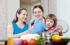 Frauen mit dem Kind, welches zusammen das Veggiemittagessen kocht Stockfotos