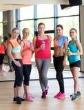 Frauen mit Flaschen Wasser in der Turnhalle Lizenzfreies Stockfoto