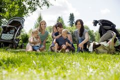 Frauen mit ihren Kindern, die Picknick genießen Lizenzfreies Stockbild