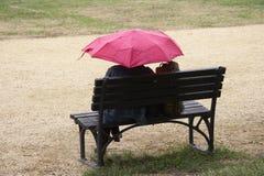 Frauen mit rosafarbenem Regenschirm Stockfotografie