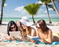 Frauen mit Tabletten-PC und -buch auf Sommer setzen auf den Strand Stockfotos