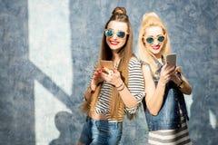 Frauen mit Telefonen zuhause Stockbild