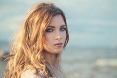 Frauen-Mode-Modell mit Make-up und dem langen gelockten Haar stockbild