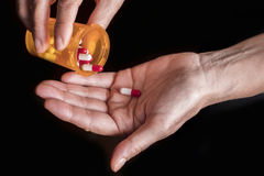 Frauen nehmen die Kapsel, die mit rechter Hand von einer Flasche rot und weiß ist Lizenzfreie Stockfotos