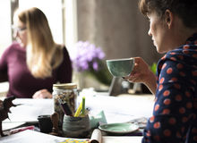 Frauen-nippender Kaffee von der Schale auf Büro Stockbilder