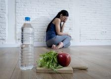 Frauen- oder Jugendlichmädchen, das zu Hause auf Boden allein gesorgter leidender Nahrungsessstörung sitzt stockfotografie