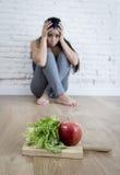 Frauen- oder Jugendlichmädchen, das zu Hause auf Boden allein gesorgter leidender Nahrungsessstörung sitzt stockfoto