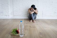 Frauen- oder Jugendlichmädchen, das zu Hause auf Boden allein gesorgter leidender Nahrungsessstörung sitzt lizenzfreie stockfotografie