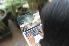 Frauen- oder Mädchenbetrachtungsseebild auf ihrem Laptop, ihre folgenden Ferien stockfotografie