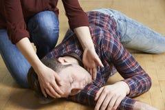 Frauen-Plazierungs-Mann in stabiler Seitenlage nach Unfall Stockbilder