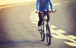 Frauen-Radfahrer-Reitmountainbike auf Stadtstraße Lizenzfreie Stockfotografie