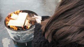 Frauen-Reibungs-Hände vor brennendem Kamin Mädchen wärmt sich während des Winters des Feuers in einem runden Fass stock video
