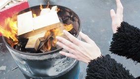 Frauen-Reibungs-Hände vor brennendem Kamin Mädchen wärmt sich während des Winters des Feuers in einem runden Fass stock video footage