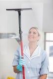 Frauen-Reinigung mit Gummifensterputzer Lizenzfreie Stockbilder
