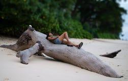 Frauen-Reisender, der auf einem gefallenen Baum auf einem Strand sich entspannt stockfoto