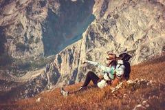 Frauen-Reisender mit dem Rucksack, der in den Bergen sich entspannt Lizenzfreies Stockfoto