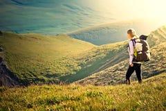 Frauen-Reisender mit dem Rucksack, der in den Bergen wandert Lizenzfreies Stockfoto
