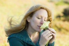 Frauen-riechende Blume lizenzfreie stockbilder