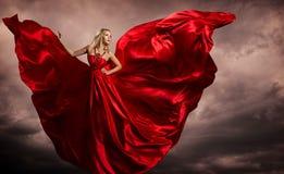 Frauen-rote Kleiderflügel, Mode-Modell Silk Waving Gown, fliegendes flatterndes Gewebe auf Sturm-Wind stockbilder