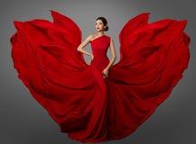 Frauen-rotes Kleid, Mode-Modell in lange Seiden-wellenartig bewegenden Kleiderflügeln, fliegendes flatterndes Gewebe stockfotos