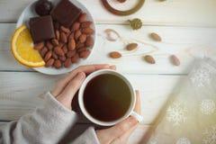 Frauen ` s übergibt das Halten eines Tasse Kaffees auf einem Holztisch Beschneidungspfad eingeschlossen Lizenzfreie Stockfotos
