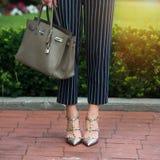 Frauen ` s Beine in den grauen Schuhen der hohen Absätze Helle graue Schuhe, Tasche und blaue Hosen Baumwollhose, stilvolle Damen Lizenzfreies Stockbild
