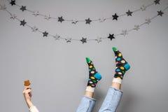 Frauen ` s Beine in den lustigen Socken und Jeans auf einem grauen Hintergrund mit dem Dekor der Sterne und des Ingwerplätzchens Stockbild