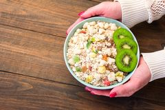 Frauen ` s Hände bieten ein gesundes Frühstückskost aus Getreide muesli mit Trockenfrüchten an Lizenzfreies Stockfoto