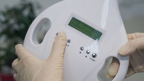 Frauen ` s Hände in den Handschuhen, die eine Zahnweißungsmaschine, neueste zahnmedizinische Bleiche Lasers anstellen stockfotografie