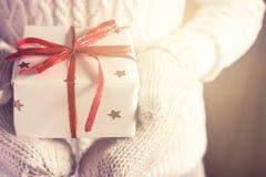 Frauen ` s Hände in den Handschuhen halten Weihnachten oder verzierte Geschenkbox des neuen Jahres Lizenzfreie Stockbilder