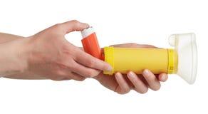 Frauen ` s Hände, die den Inhalator und das aerochamber lokalisiert auf wh halten Stockbilder