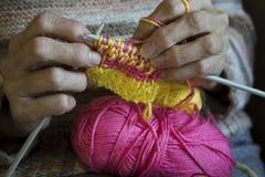 Frauen ` s Hände halten Stricknadeln und einen gelben Thread, um zu binden stockbild