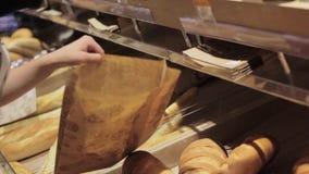 Frauen ` s Hände legen einen Brotlaib in einem Kasten stock video