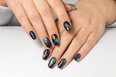Frauen ` s Hände mit einem abstrakten Muster auf den Nägeln stockfoto